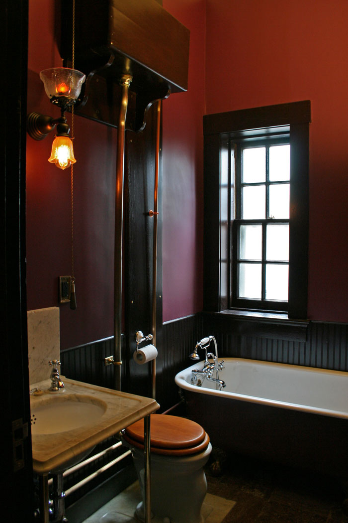 The renovated bathroom, wainscoting, fixtures and granite floor restored.