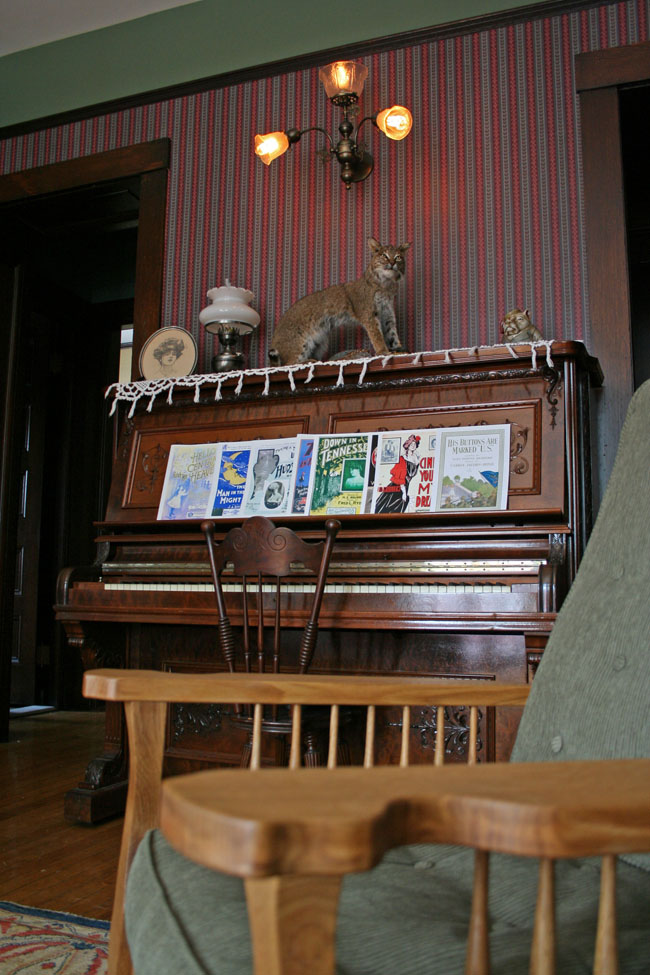 Our piano, festooned with period tunes. That's Johnny the bobcat, by the way, our mascot; beneath his sharp claws poor old Eli is down for the count